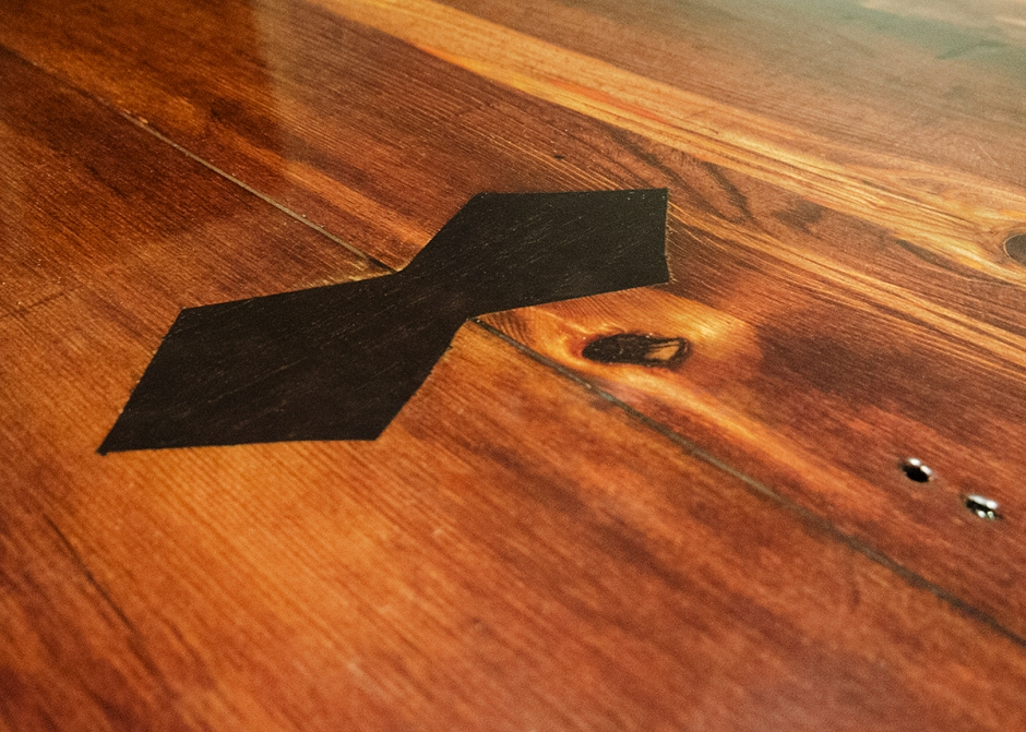Custom bow tie joints are utilized to secure cracks in the lumber and increase the longevity of the table.