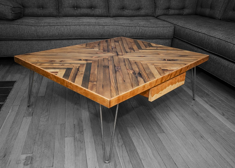 This is a coffee table created using reclaimed old growth lumber that has been ebonized, creating the variance in color.  The trim and the drawer are made from American Cherry. The legs are stainless steel hairpin legs.